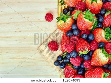 Strawberry and mix berry on wooden background top view