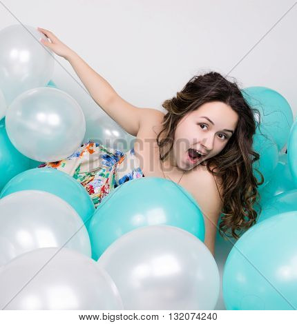 beautiful curly girl in a multi-colored dress playing with balloons.