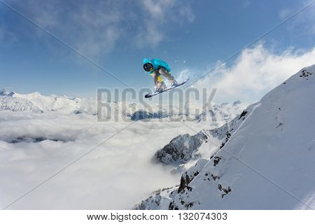 Snowboard rider jumping on mountains. Extreme snowboard freeride sport.