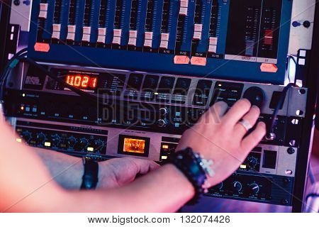 DJ adjusts sound panel in the sound recording studio. Sound producer adjusts music equipment before starting work.  Sound engineer checks the sound panel.  Digital sound equipment service concept