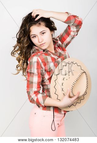 beautiful curly girl in pink pants, a plaid shirt and cowboy hat