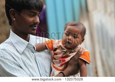 A portrait of a poor Indian father holding his little son looking at him lovingly.