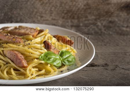 Spaghetti carbonara on white plate on rustic wooden background and copy space