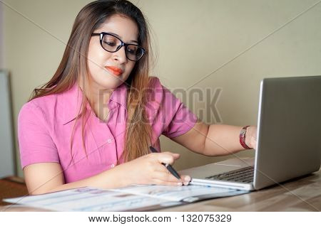 Indian Young businesswoman working with laptop in office. The business woman reading something in her laptop and taking notes with pen and notepad.