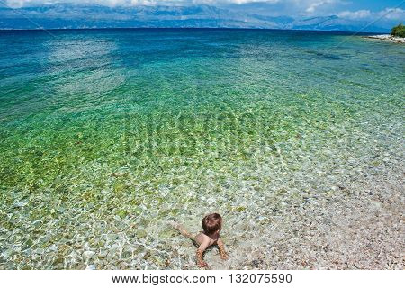 Little boy swimming and looking at the wide sea