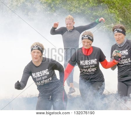 STOCKHOLM SWEDEN - MAY 14 2016: Blonde group woman and man of people running through fire and smoke in the obstacle race Tough Viking Event in Sweden April 14 2016