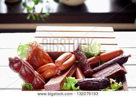 Sausage variety in wooden box. Close-up of delicious sausage assortment in the box. Plenty of sausages decorated with lettuce.