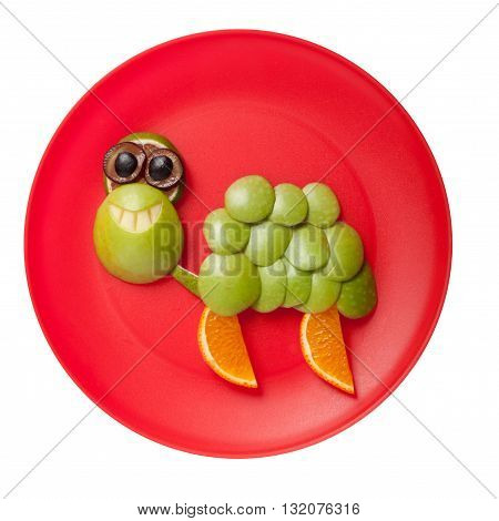 Funny smiling turtle made of fruits on plate