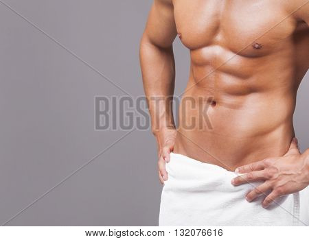 Fit man in towel on grey background