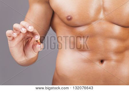 Muscular man holding a pill on grey background