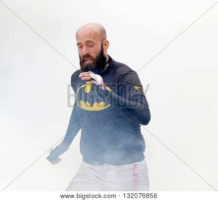 STOCKHOLM SWEDEN - MAY 14 2016: Bald man with beard running through fire and smoke in the obstacle race Tough Viking Event in Sweden April 14 2016