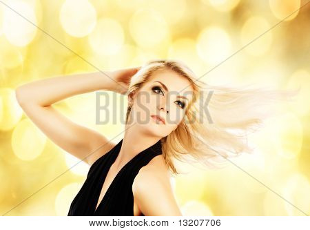 Beautiful blond woman over abstract golden background