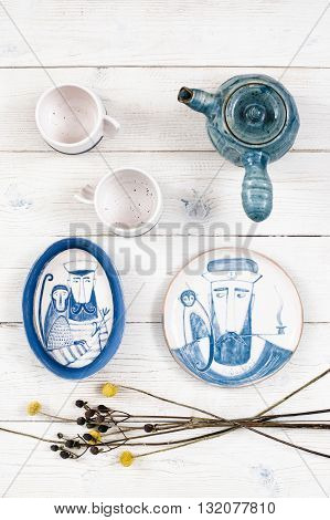 Flat lay of two cups, teapot and two same way painted plates on white wooden background. Plates with sailor and monkey on his shoulder. Marine concept of serving tea-party top view
