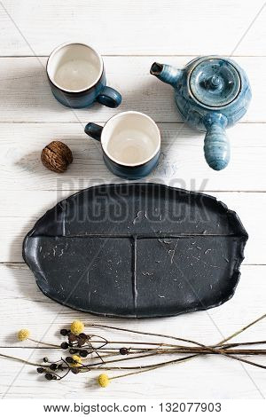 Serving tea for two on white wooden background. Top view on composition of two clay cups, clay teapot and black clay plate, decorated dry flowers.