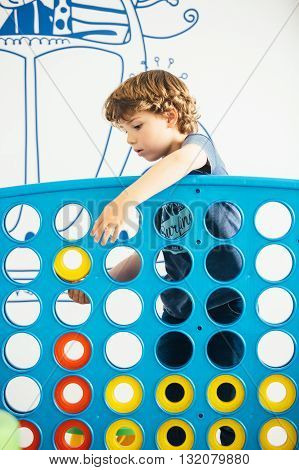 Portrait of curly-haired cute boy playing educational game in kindergarten