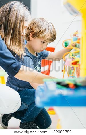 Side view of adorable boy playing at home with his mom near