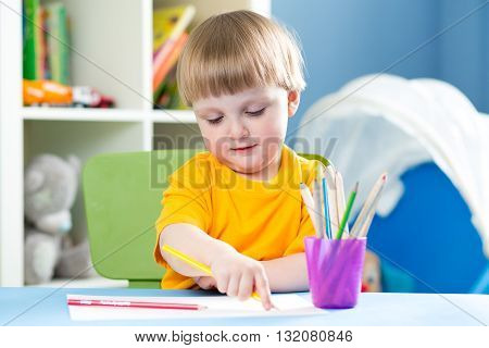 Cute child boy is drawing with color pencils in nursery room