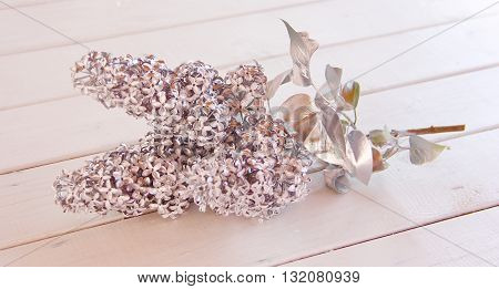 Silver flowers and leaves, branch of lilac on a white table, unique, unusual solution for plants