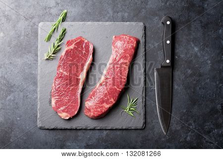 Raw striploin steak and kitchen knife over stone table. Top view