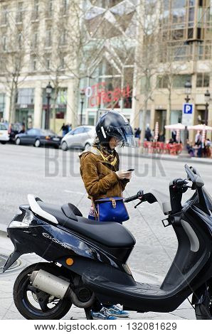 Paris France - March 19 2012: Young woman controls his mobile phone before boarding the motor scooter in the Avenue des Champs-Elysees Paris.