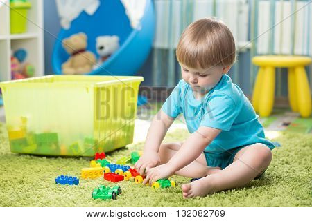 kid boy plays with building blocks at home or kindergarten
