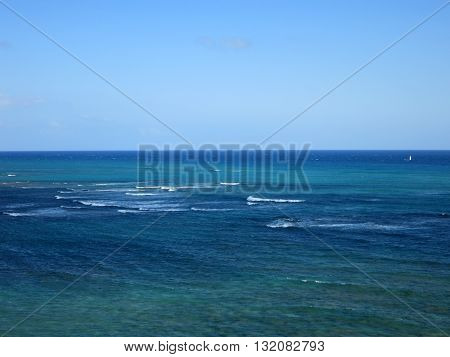 Shallow wavy ocean waters of Waikiki looking into the pacific ocean with sail boat on water blue sky and clouds on Oahu.