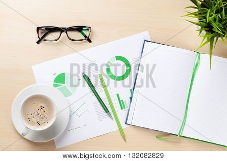 Office desk workplace with charts, coffee cup, plant and notepad on wooden table. Top view with copy space