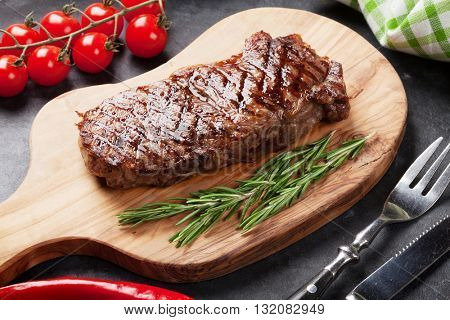 Grilled beef steak on cutting board over stone table
