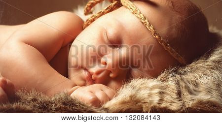 Newborn sleeping baby in wooden box with sunflower and onion. Cute newborn girl with pumpkin and fur.