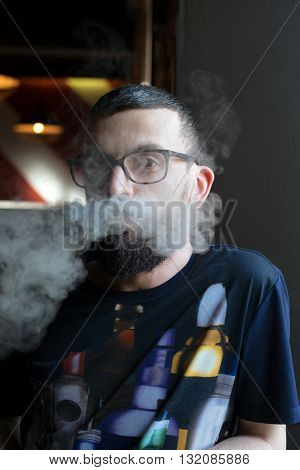 Man With Glasses In The Smoke Of The Vaporizer
