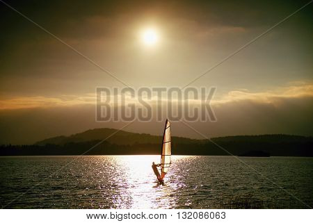 Windsurfer Sailing Into Breeze Shot With Gentle Filter. Strong Sun Makes Reflections.