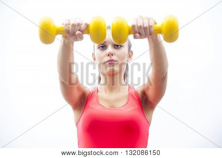 young female athlete lifting yellow dumbbells outdoor