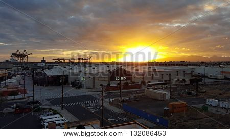 HONOLULU - APRIL 10: Sunset over Lowe's and Shipping Cranes with Matson Shipping containers around building on Oahu Hawaii April 10 2016. Lowe's Companies Inc. is an American company that operates a chain of retail home improvement and appliance stores
