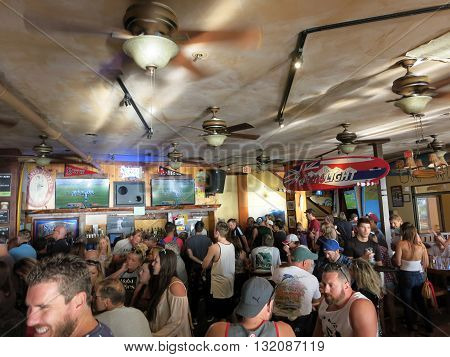 WAIKIKI OAHU - FEBRUARY 7: Crowd People watch Superbowl 50 game at iconic Lulu's Bar. SupeBowl the most watch game in the world. taken February 7 2016 Waikiki Hawaii.