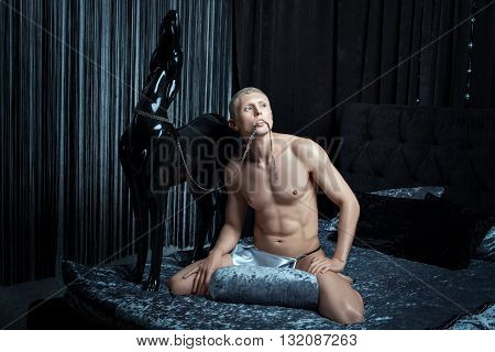 Metrosexual man playing sitting on a bed.