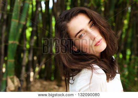 Attractive Young Woman Tilting Head In Front Of Bamboo