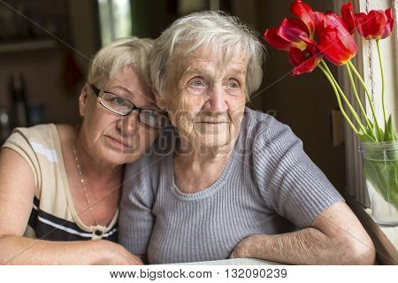 Two women, an old mother and her adult daughter sit together near the window.