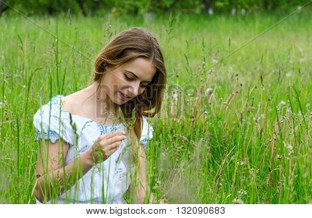 Young beautiful woman sitting in the meadow grass