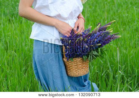 Girl with wicker basket of meadow flowers in green field