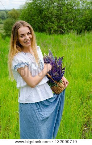 Beautiful girl with basket of meadow flowers in hands