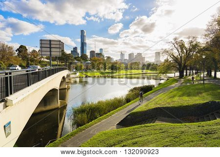 Melbourne, Australia - May 24, 2016: People cycling and jogging in the park along Yarra River in Melbourne CBD