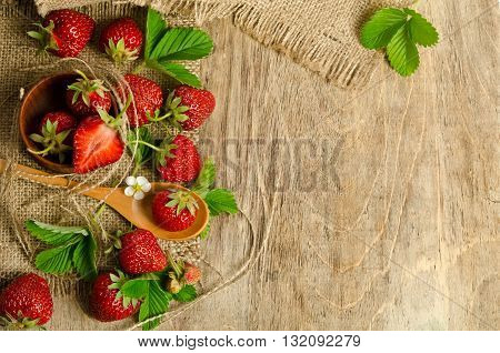 Strawberries with leaves on wooden background from right side