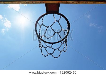 Basketball hoop with chains on sunny blue sky background