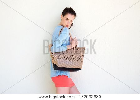 Fashionable Young Woman Holding Purse Against White Wall