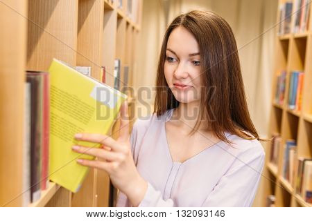 Young student takes the yellow book in the student library from the rack
