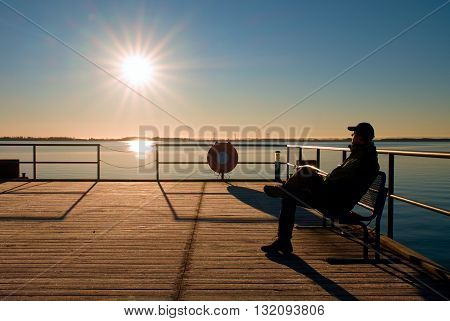 Man Sit On Bench On Wharf Construction And Looking At Sea. Sunny Blue Sky, Smooth Level