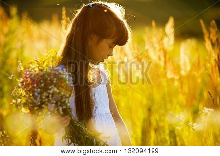 Little girl with a bouquet of wild flowers