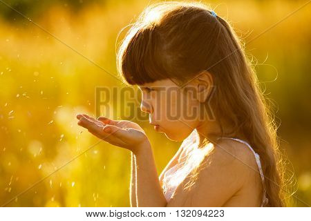 Little girl blowing on seeds in the palms