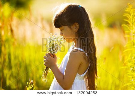 Little girl with a bouquet of wildflowers