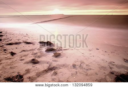 Wooden breakwater in wavy Baltic Sea. Romantic atmosphere at smooth wavy sea. Pink horizon with first hot sun rays.